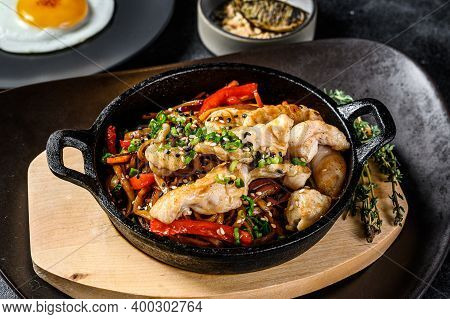Udon Stir Fry Noodles With Chicken And Vegetables In Pan. Black Background. Top View