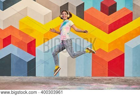 Happy Young Female With Stains Of Paint Listening To Music In Headphones And Leaping Against Wall Wi