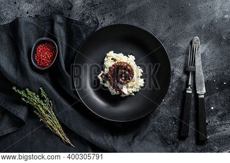 A Portion Of Risotto With Octopus Tentacles. Black Background. Top View