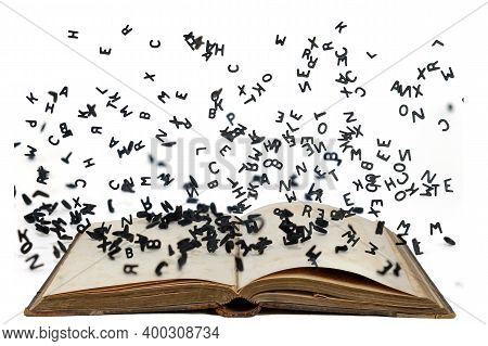 Letters Of The Alphabet In Levitation In The Air Over The Open Book