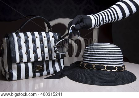 Stripped Black And White Woman's Hat And Lady's Purse On Table. Female Hand Holding Stylish Glasses.