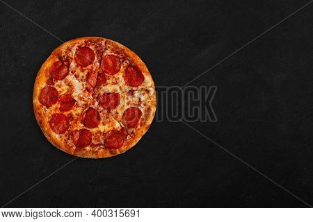 Tasty Pizza With Salame On Dark Concrete Surface With Place For Your Text. Top View Of Pepperoni Sli