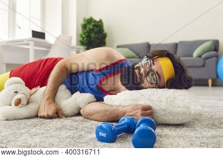 Lazy Bearded Man Lying On The Floor Near Dumbbells And Napping Instead Of Training.