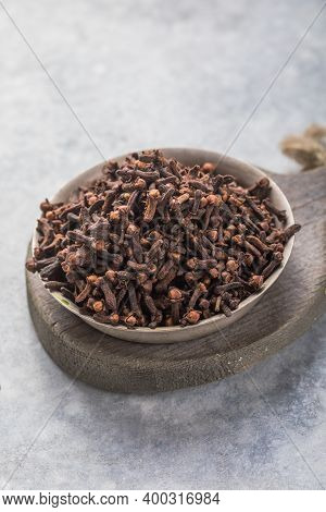 Spice Dry Cloves On  Stone Background With Copy Space. Dried Cloves In A Bowl Over Wooden Background