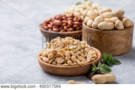 Roasted Salted Peanuts. Crispy Nuts In Bowl On Stone Table.roasted Peanuts On A Wooden Bowl And Sack