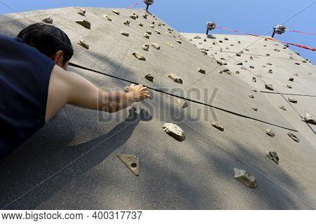 Sportman Climbing On The Rock Wall