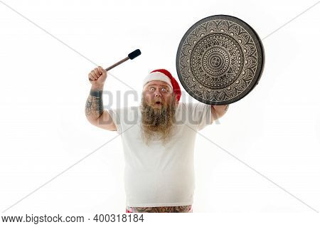 An Overweigh Man Shaman With Tattooed Arms In Santa Claus Hat Dancing With A Shaman Tambourine And E