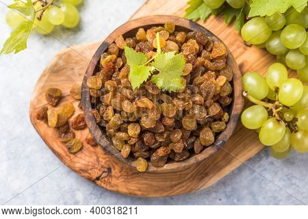Golden Raisins  In Bowl On Stone Background, Table Top View. Dried Fruit, Healthy Snack Food. Dry Go