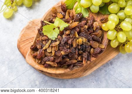 Golden Raisins  In Bowl On Stone Background, Table Top View. Dried Fruit, Healthy Snack Food. Black