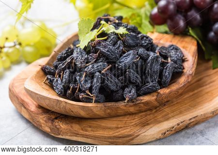 Black Raisins  In Bowl On Stone  Background, Table Top View. Dried Fruit, Healthy Snack Food. Black