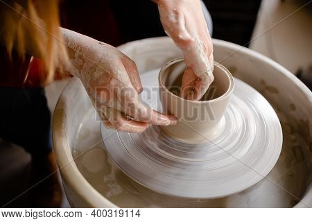 Female Hands Crafting A Pottery Cup On A Potters Wheel. Handmade And Crafting Concept. Top Horizonta
