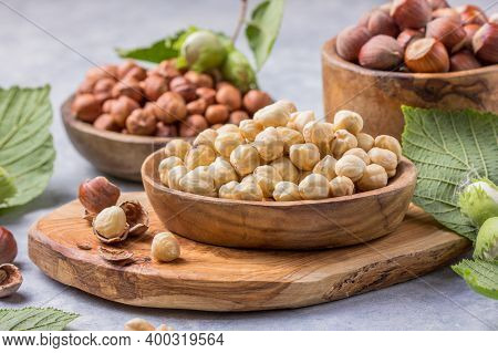 Hazelnuts With Peeled Hazelnut And Leaf  In Brown Bowl On Concrete Background.hazelnuts In On Rustic