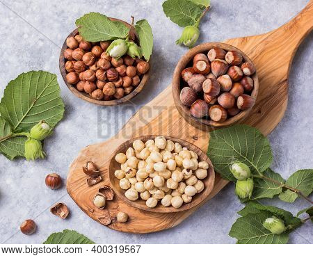 Top View Of Hazelnuts With Peeled Hazelnut And Leaf  In Brown Bowl On Concrete Background.hazelnuts