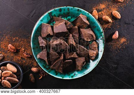 Broken pieces of dark chocolate in a vintage bowl and cocoa beans on a dark textured background, top view. Confectionery chocolate background. Chunks of chocolate.