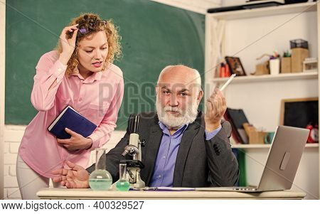 Teacher And Girl With Notepad Near Chalkboard. College University Education. Biology Science. Biolog