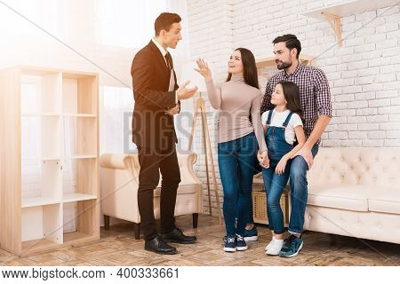 Realtor In Suit Shows Family House They Bought. Concept Of Buying House. Buying Real Estate.