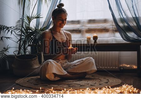 Young Woman Sitting On The Floor, Lights Candles, Enjoy Meditation, Do Yoga Exercise At Home. Mental