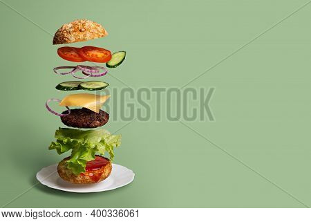 Delicious Burger With Flying Ingredients On A Light Green Background. Concept Of Food Levitation Cop