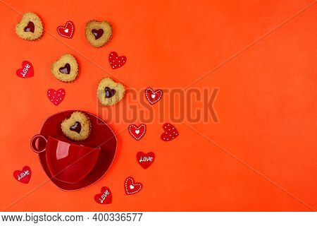 Red Cup With Saucer And Linzer Cookies Heart Shape Cookies On Red Background. Valentine's Day Greeti