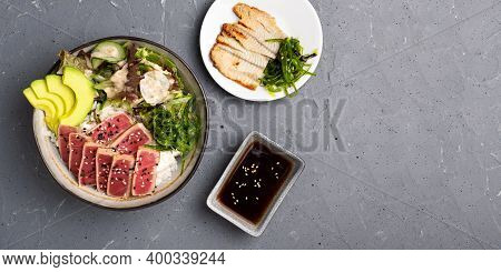 Poke Salad With Tuna, Rice And Chuka Seaweed In A Deep Bowl On A Gray Background. Next To It Is A Wh