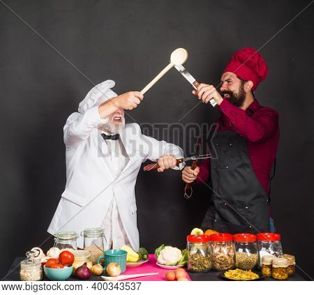 Kitchen. Two Chefs Fighting. Beared Chef Man. Delicious Food. Male Chef In Uniform. Satisfied Bearde