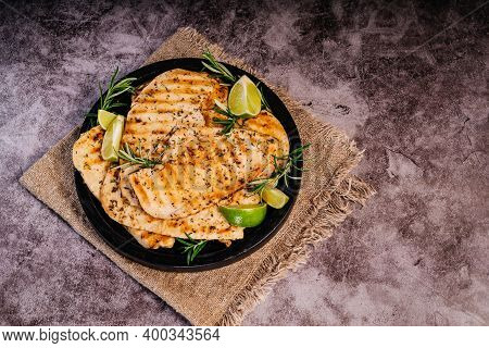 Grilled Chicken Fillet On A Black Plate With Lime Pieces And Fresh Rosemary.grilled Chicken Fillet O
