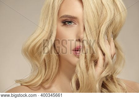 Female Beauty, Hairstyle Of Blonde Long Wavy Hair. Caucasian Attractive Woman Has A Natural Curly Ha