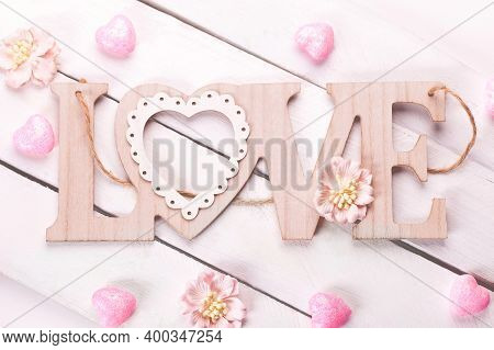 Wooden Background With The Word Love, Pink Hearts And Flowers