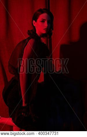 Glamorous young woman in fashionable black dress stands in a luxury apartment in red light. Beauty, fashion concept. Glamorous lifestyle.
