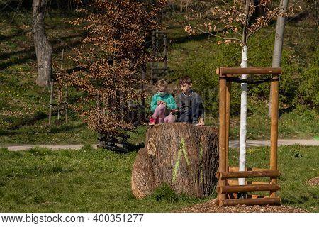 Prague, Czech Republic. 03-11-2020. Two Small Kids Having A Conversation Sitting On A Tree Trunk. Co