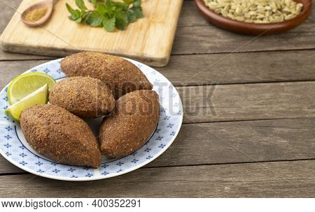 Traditional Arabic Fried Kibbeh Over Wooden Table With Copy Space. Typical Brazilian Snack.