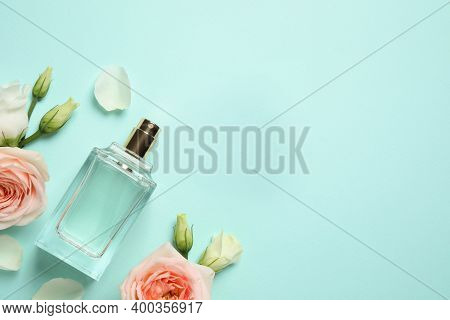 Flat Lay Composition With Bottle Of Perfume And Flowers On Cyan Background, Space For Text