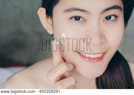 Cropped Shot View Of Young Asian Woman Applying Acne Cream/moisturizer On Her Face. Conceptual Of Be