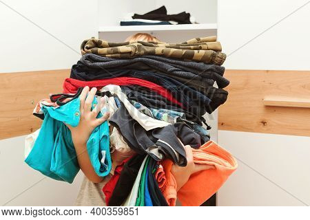 Boy Holding A Huge Pile Of Clothes. Kid Makes Order In The Closet. Storage Organization.