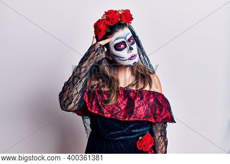 Young woman wearing day of the dead costume over white pointing unhappy to pimple on forehead, ugly infection of blackhead. acne and skin problem