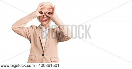 Young blonde woman wearing business clothes and glasses doing ok gesture like binoculars sticking tongue out, eyes looking through fingers. crazy expression.