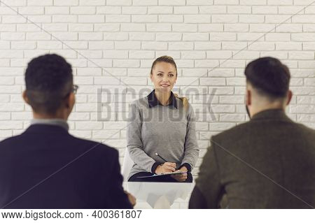 Female Recruiting Specialist Sitting And Listening To Presentation Of Candidate During Interview