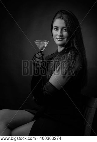 Attractive Girl Drinking Dry Martinis With Green Olives. Beautiful Brunette In Black Holding Glass W