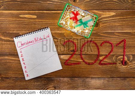 Christmas Composition Grocery Basket With Gifts, Garland, Wish List And Numbers 2021 New Year On A W
