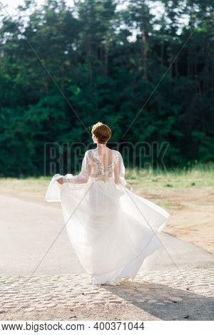 Pretty Young Caucasian Redhead Girl In Garden And Outside With Wedding Bouquet.