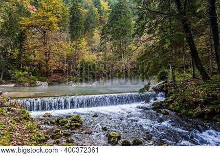 Picturesque shallow lake with glacial greenish water. Artificial waterfall - dam.  Autumn forest in a mountain valley. Light fog rises above the water. Julian Alps, Slovenia