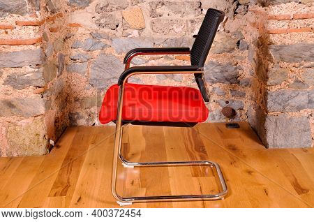 Comfortable And Stylishly Designed Red And Black Office Chair In Front Of A Wall