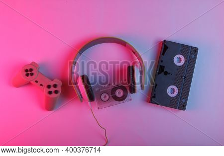 Retro Media And 80s Entertainment. Headphones, Audio Cassette, Video Cassette, Gamepad. Neon Pink-bl