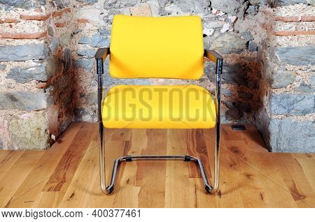 Comfortable And Stylishly Designed Yellow Office Chair In Front Of A Wall