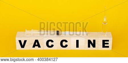 Injection And Ampoule With Vaccine. Covid19 Pandemics. Vaccine In Wooden Cubes.