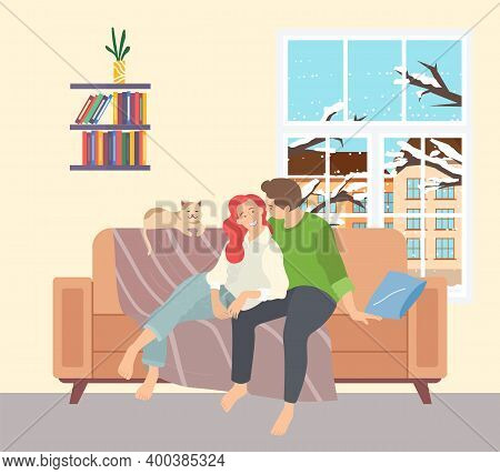 A Young Couple Sits At Home In The Winter On The Couch Near The Window. A Man And A Woman Spend Thei