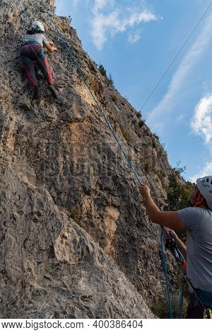 Girl Climbing A Rock Wall Looking For The Best Grip Laterally While Her Partner Belays Her From Belo