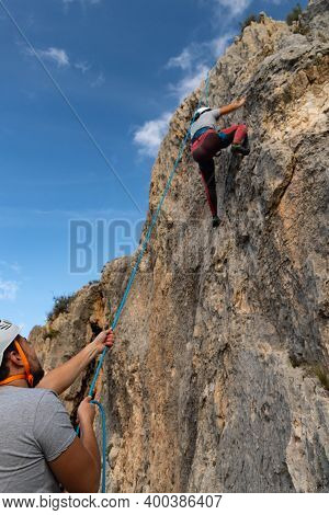 Girl In The Middle Of A Rock Wall That Is Climbing While Her Boyfriend Belays Her From Below