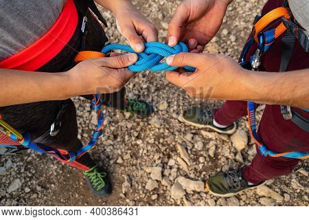 Hands Of A Couple Of Climbers Making The Eight Knot In Her Harness To Start Climbing. Working As A T