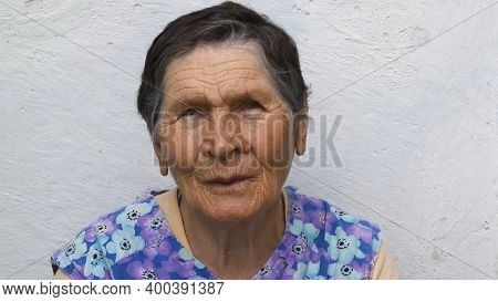 Authentic Portrait Of 80 Years Old Lady Of Mixed Ethnicity. Wrinkled Face Of Elderly Woman With Conc